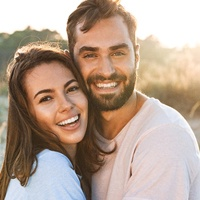 Smiling couple with beautiful, healthy teeth standing outside