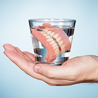 Full denture in glass of water