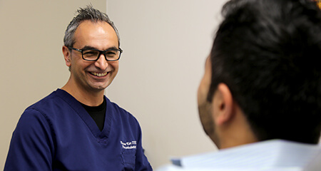 Dr. Kar smiling at dental patient