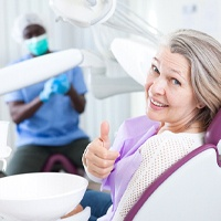 Older woman in dental chair giving thumbs up