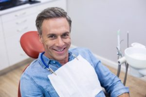 Happy patient at appointment to maximize dental insurance benefits