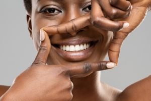 Woman using fingers to frame smile with dental implants in Allen